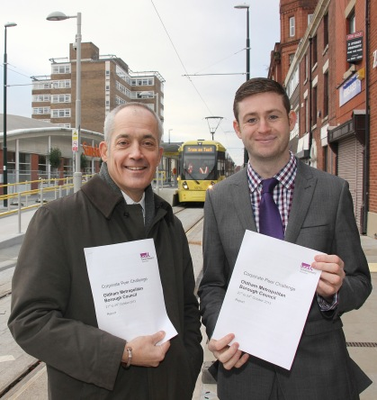 FULL SPEED AHEAD:  Jim McMahon and Charlie Parker pictured with the new report as trams are tested on Oldham's new Metrolink line.
