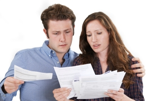 Studio Shot Of Worried Couple Looking At Bills